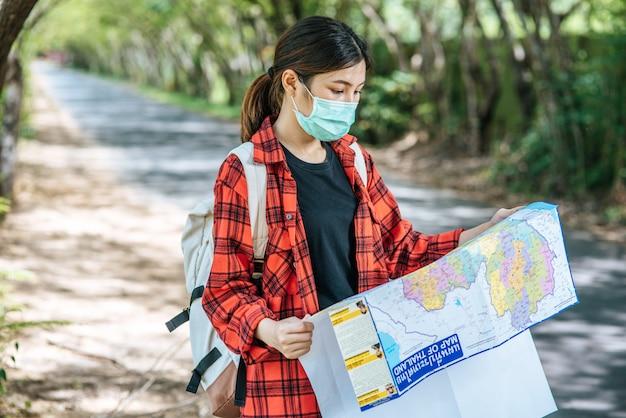 As mulheres turistas ficam e olham para o mapa na estrada.