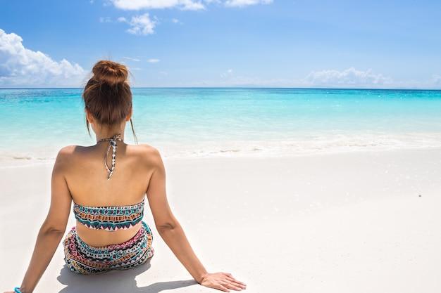 As mulheres usam biquíni sentado na praia