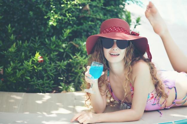 As mulheres usam biquínis e bebem coquetéis no verão quente na piscina.