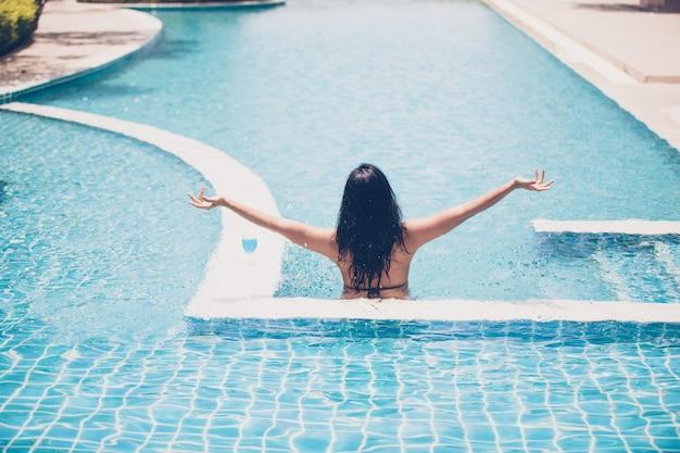 As mulheres usam biquínis e beber cocktails no verão quente na piscina
