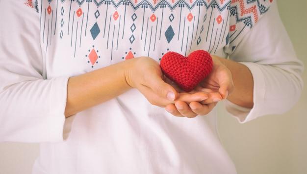 As mulheres usam camisa branca, mão segurando um coração vermelho.