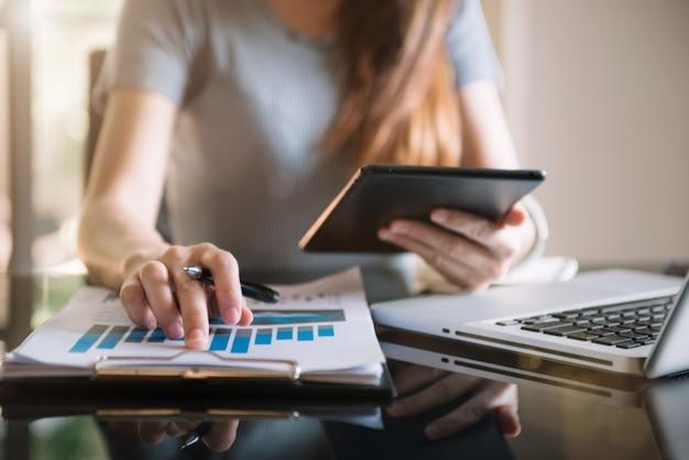As mulheres usam o tablet e papéis de trabalho na mesa do escritório pela manhã
