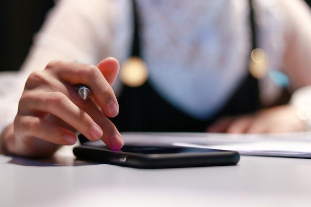 As mulheres usam telefone inteligente estão trabalhando no meio da noite.
