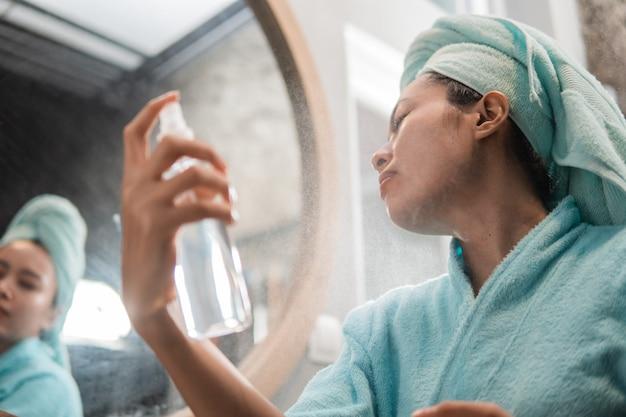 As mulheres usam uma toalha ao borrifar um hidratante para a pele facial com um frasco de spray na frente do vidro
