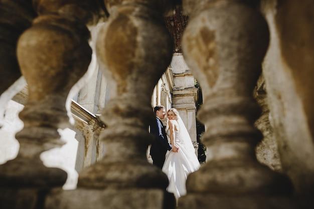 As noivas encantadoras em pé perto de um edifício antigo