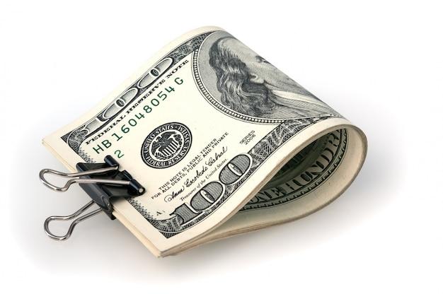 As notas de cem dólares são dobradas e grampeadas. fundo branco. isolado.