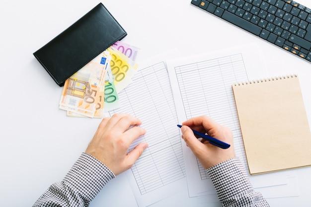 As notas de euro estão empilhadas. homem fazendo sua contabilidade. distribuição de despesas em uma pequena empresa. poupança, depósito, empréstimo e taxa de juros.