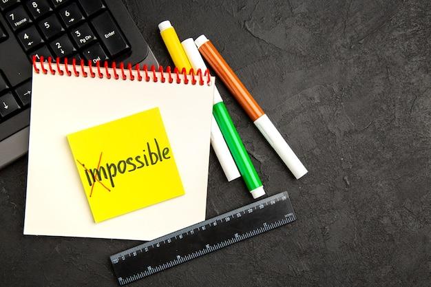As notas de motivação da vista superior com teclado e lápis na superfície escura caneta fotográfica caderno de notas caderno escolar cores inspiram