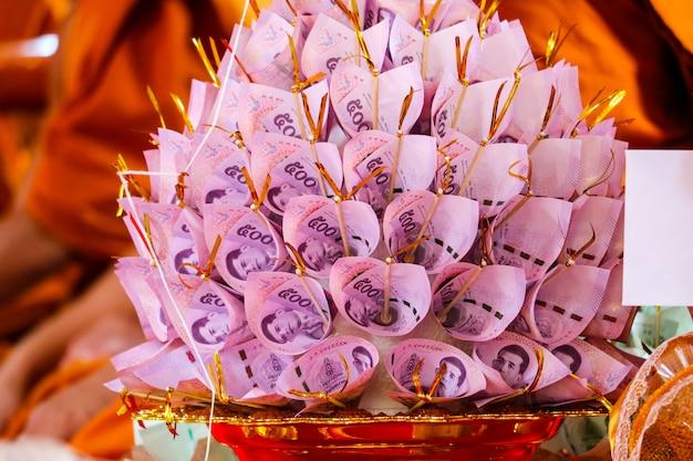 As notas são finamente dobradas para decorar o prato de golen para dar ao templo budista