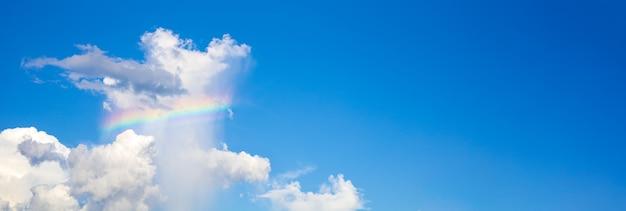 As nuvens brancas têm arco-íris coloridos no céu azul brilhante durante o dia.