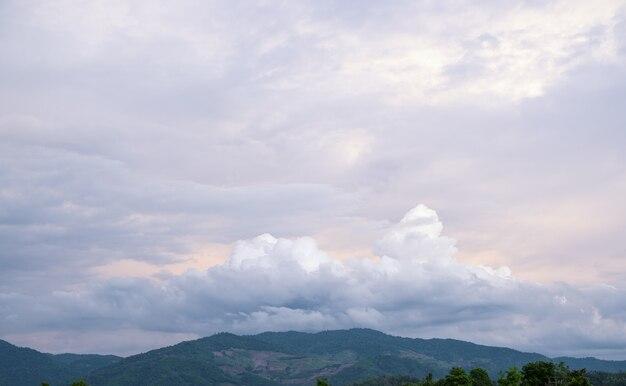 As nuvens brancas têm uma forma e uma montanha estranhas. o céu e o espaço aberto têm montanhas abaixo. nuvens flutuando sobre as montanhas.