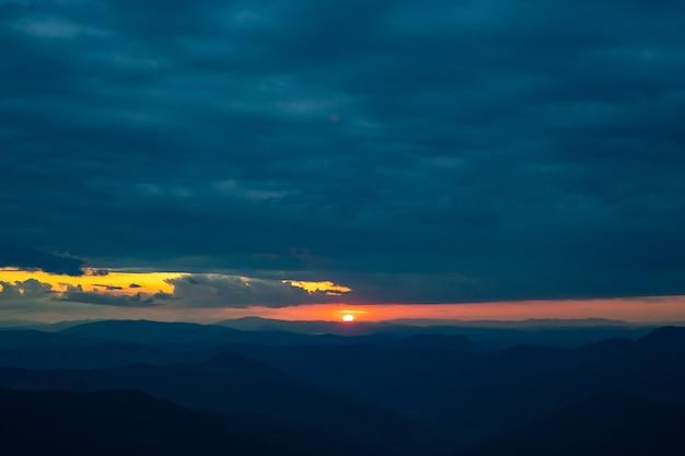 As nuvens chuvosas acima da paisagem montanhosa em um fundo do nascer do sol