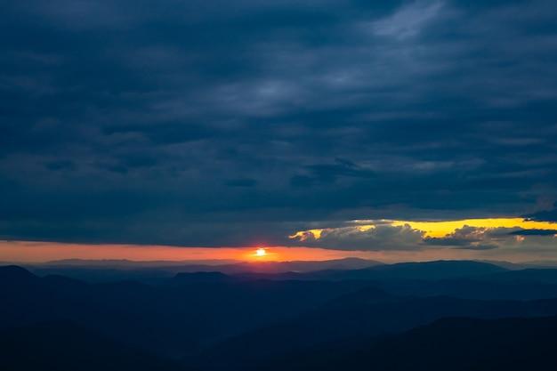 As nuvens chuvosas acima da paisagem montanhosa em um fundo do sol
