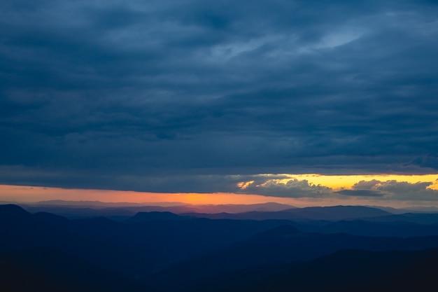 As nuvens chuvosas acima da pitoresca paisagem montanhosa em um fundo do pôr do sol