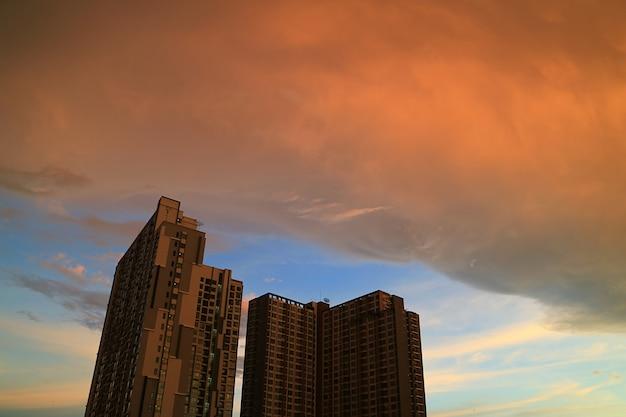 As nuvens de chuva com reflexos do entardecer do sol rolar no edifício em bangkok, tailândia