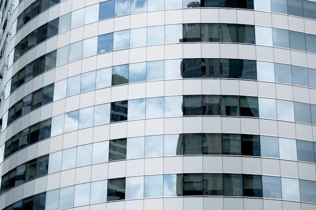 As nuvens refletiram nas janelas do prédio de escritórios moderno.
