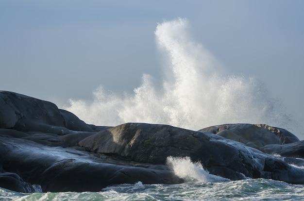 As ondas atingem as falésias em um dia ventoso à beira-mar.