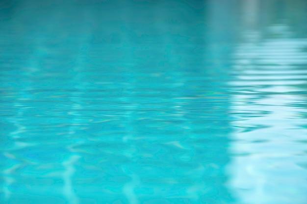 As ondas de água azul pelo vento e pela luz solar que refletem a superfície na piscina.