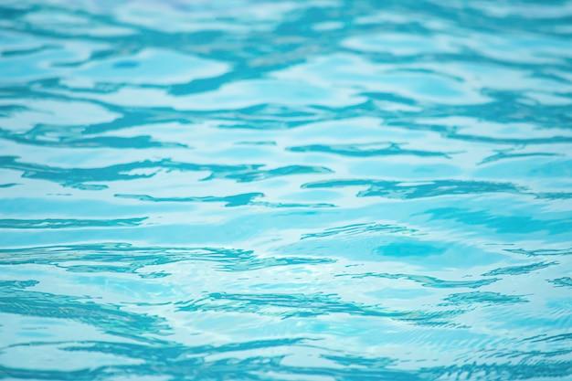 As ondas de água azul pelo vento e pela luz solar refletindo a superfície