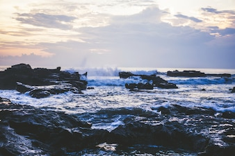 As ondas do oceano estão quebrando contra as rochas. espirrando ondas do mar ao pôr do sol.