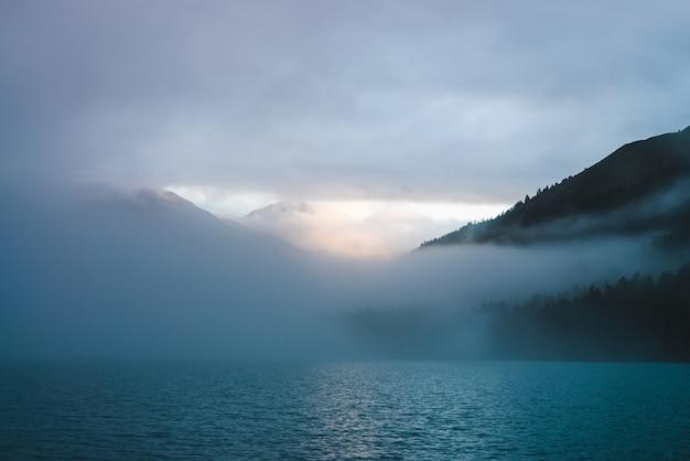 As ondinhas no lago da montanha surgem na névoa na hora dourada. sol brilha através de densas nuvens baixas nas montanhas. trilha ensolarada brilha na água ao nascer do sol. alpino cenário relaxante com nevoeiro em tons pastel.