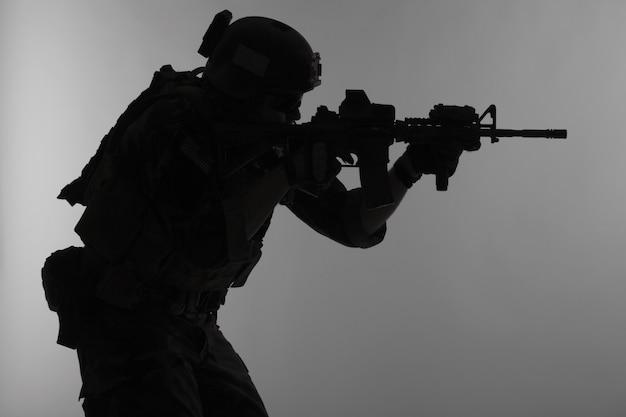 As operações especiais do corpo de fuzileiros navais dos estados unidos comandam o marsoc raider com arma apontando uma arma. fundo cinza da silhueta do operador especial marinho