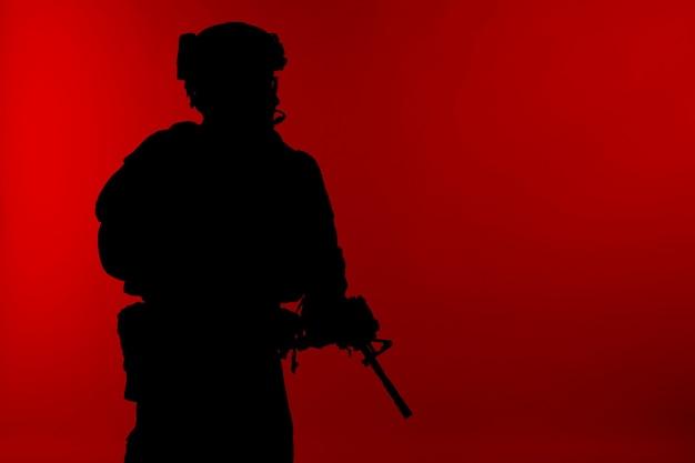 As operações especiais do corpo de fuzileiros navais dos estados unidos comandam o marsoc raider com arma. silhueta de fundo vermelho do operador especial marinho