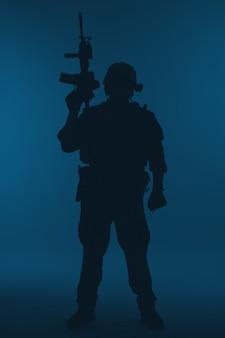As operações especiais do corpo de fuzileiros navais dos estados unidos comandam o marsoc raider com arma. silhueta do operador especial marinho de fundo azul de corpo inteiro