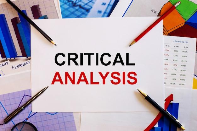 As palavras análise crítica são escritas em uma superfície branca perto de gráficos coloridos, canetas e lápis