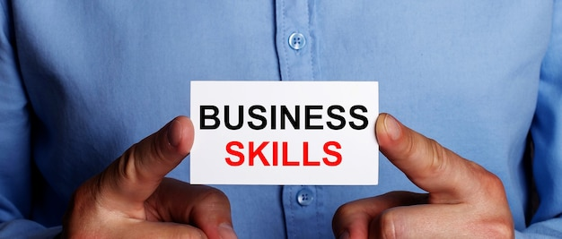 As palavras business skills estão escritas em um cartão de visita branco nas mãos de um homem. conceito de negócios.