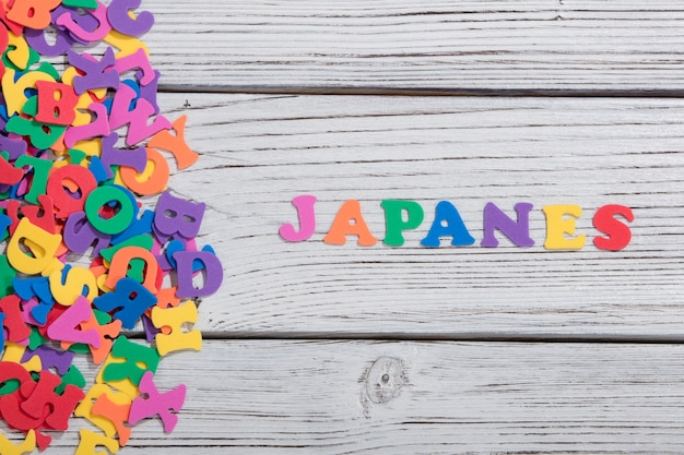 As palavras coloridas japonesas feitas com letras coloridas em uma placa de madeira branca