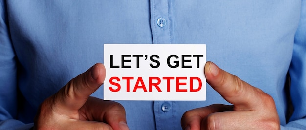 As palavras começamos estão escritas em um cartão de visita branco nas mãos de um homem. conceito de negócios