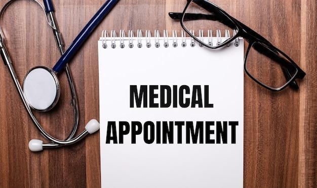 As palavras consulta médica estão escritas em papel branco sobre um fundo de madeira perto de um estetoscópio