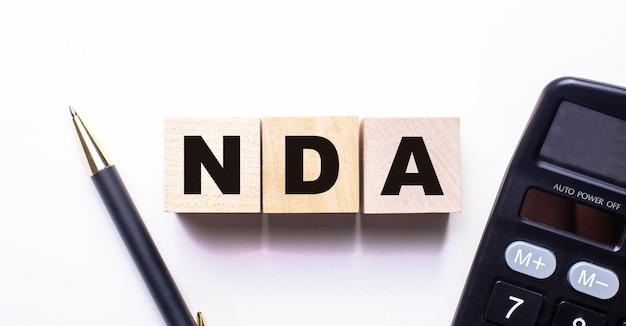As palavras contratos de não divulgação do nda estão escritas em cubos de madeira entre uma caneta e uma calculadora em um fundo claro
