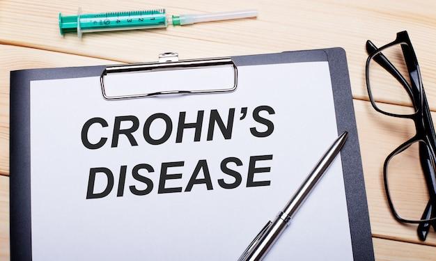 As palavras crohn é doença estão escritas em um pedaço de papel branco ao lado de óculos de aro preto, uma caneta e uma seringa