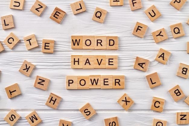 As palavras da frase têm poder no piso de madeira. blocos de letras do alfabeto no fundo.
