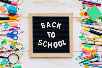 As palavras de volta à escola, escrita em giz na mesa da escola com material escolar, close-up