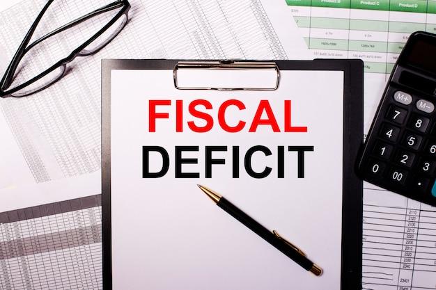 As palavras deficit fiscal estão escritas em uma folha de papel branca, perto dos óculos e da calculadora.