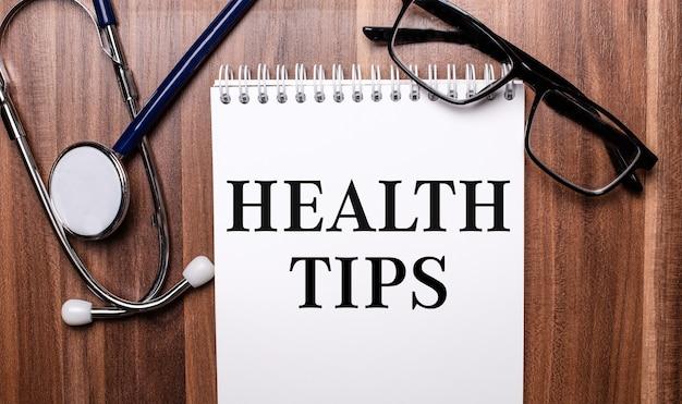 As palavras dicas de saúde estão escritas em papel branco em uma superfície de madeira perto de um estetoscópio e óculos de armação preta. conceito médico