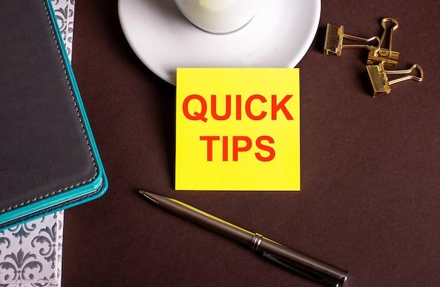 As palavras dicas rápidas escritas em papel amarelo em um fundo marrom perto de uma xícara de café e diários