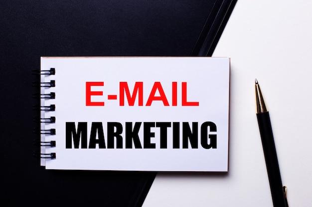 As palavras e-mail marketing escritas em vermelho em um fundo preto e branco perto da caneta