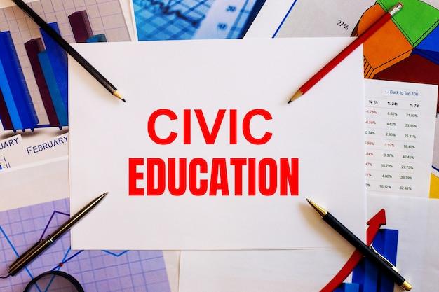 As palavras educação cívica estão escritas em um fundo branco perto de gráficos coloridos, canetas e lápis. conceito de negócios