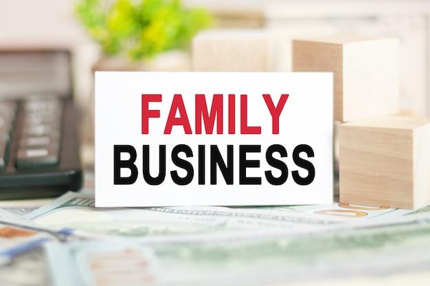 As palavras empresa familiar estão escritas em um cartão de papel branco perto de cubos de madeira, notas, calculadora preta e planta verde atrás