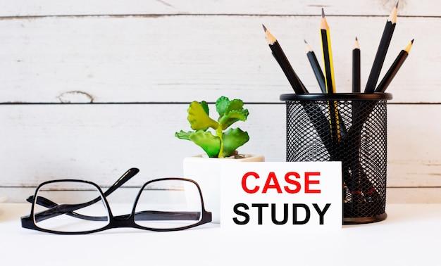 As palavras estudo de caso escritas em um cartão de visita branco ao lado de lápis em um suporte e óculos. perto está um vaso de planta.