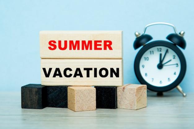 As palavras férias de verão escritas em cubos de madeira com despertador.