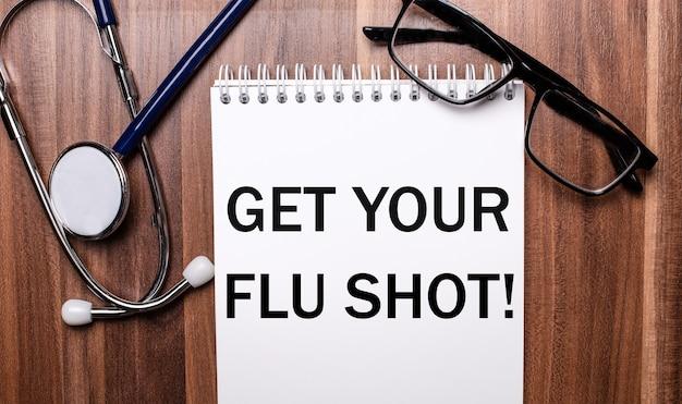 As palavras get your flu shot estão escritas em papel branco em uma superfície de madeira perto de um estetoscópio e óculos de armação preta