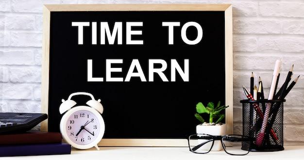 As palavras hora de aprender estão escritas no quadro-negro ao lado do despertador branco, óculos, vasos de plantas e lápis em um suporte
