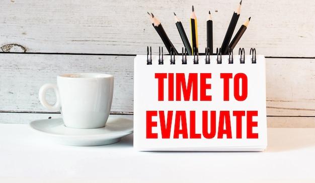 As palavras hora de avaliar estão escritas em um bloco de notas branco perto de uma xícara de café branca em uma superfície clara