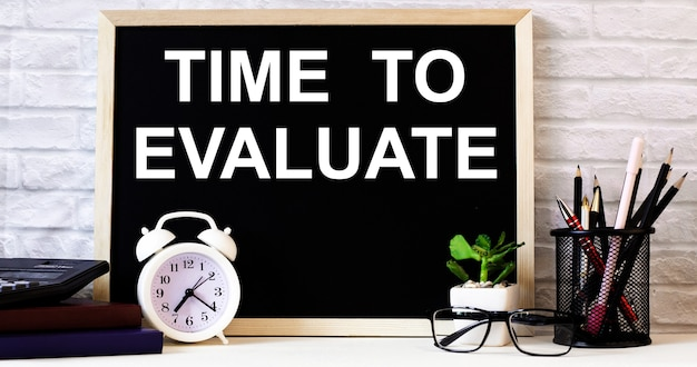As palavras hora de avaliar estão escritas no quadro-negro ao lado do despertador branco, óculos, vasos de plantas e lápis em um suporte