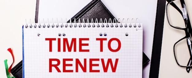 As palavras hora de renovar estão escritas em vermelho em um caderno branco ao lado de óculos de armação preta.